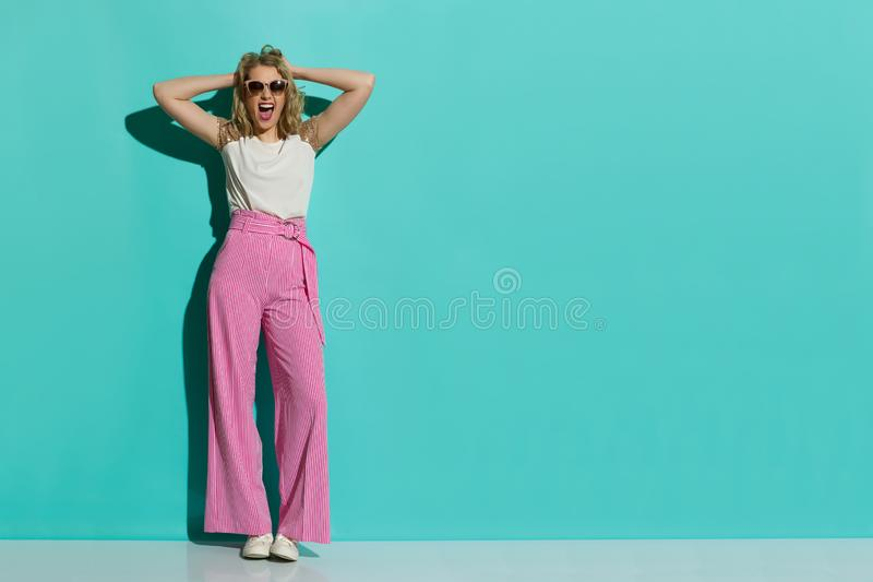 红色镶边宽腿长裤的呼喊的时尚妇女在手上拿着头 免版税库存图片