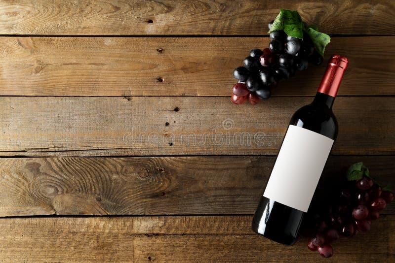 红酒酒瓶用在棕色土气木桌平的位置的葡萄从上面 免版税图库摄影