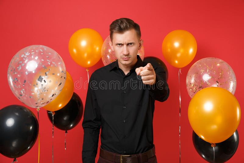 经典衬衣的严肃的严密的年轻人指向在照相机的食指在红色背景气球 St华伦泰` s 免版税库存照片