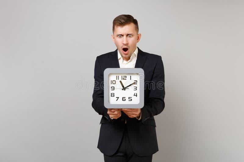 经典黑衣服的震惊年轻保持嘴的商人和衬衣大开,看在被隔绝的方形的时钟  库存照片
