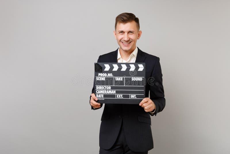 经典黑衣服的,对经典黑电影制作clapperboard负的衬衣微笑的年轻商人被隔绝在灰色 免版税图库摄影