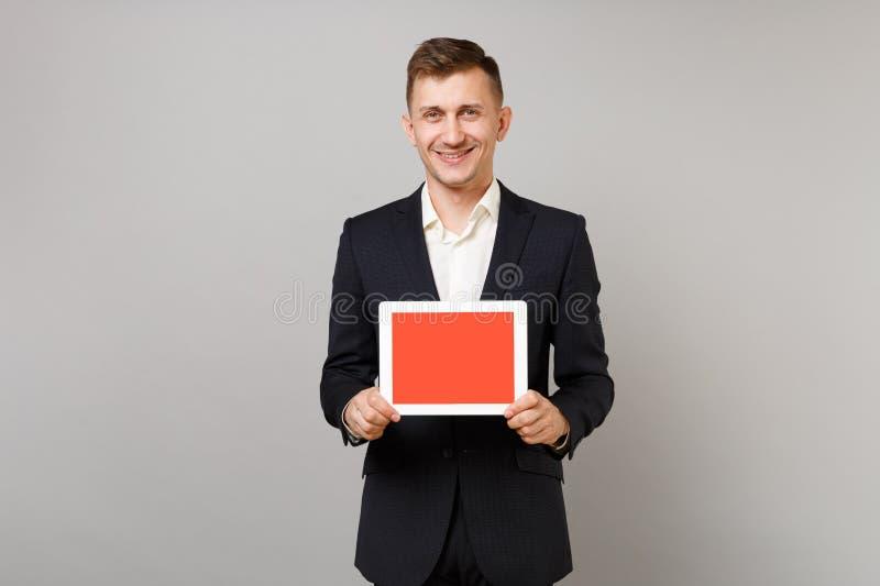 经典黑衣服的,拿着有空白的空的屏幕的衬衣微笑的年轻商人平板电脑计算机被隔绝  库存照片