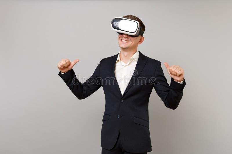 经典黑衣服的,看在耳机的衬衣微笑的年轻商人,指向在他自己的拇指在灰色隔绝了 免版税库存图片