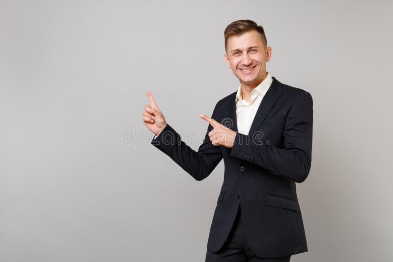 经典黑衣服的,衬衣指向食指的微笑的年轻商人画象在旁边隔绝在灰色 免版税库存图片