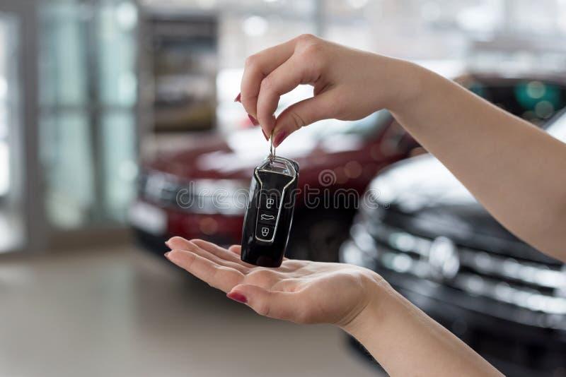 经销商妇女在她的手上把握关键到新的汽车 现代和有名望的车 免版税库存照片