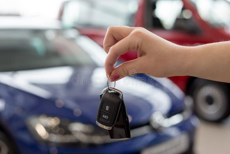 经销商妇女把握关键到一辆新的汽车 现代和有名望的车 免版税库存图片