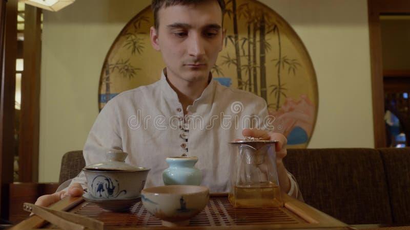绿茶的主要倾吐的注入从gaiwan的到公正碗正面图 免版税图库摄影