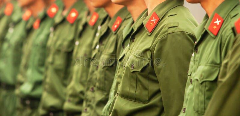 绿色制服,红色星和连续发怒剑象的年轻男性越南士兵在肩膀的丝带 越南语 免版税库存图片