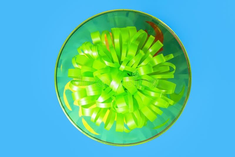 绿色玛格丽塔酒玻璃党定期的几乎抽象顶视图与绿色弓里面的在蓝色背景 库存照片