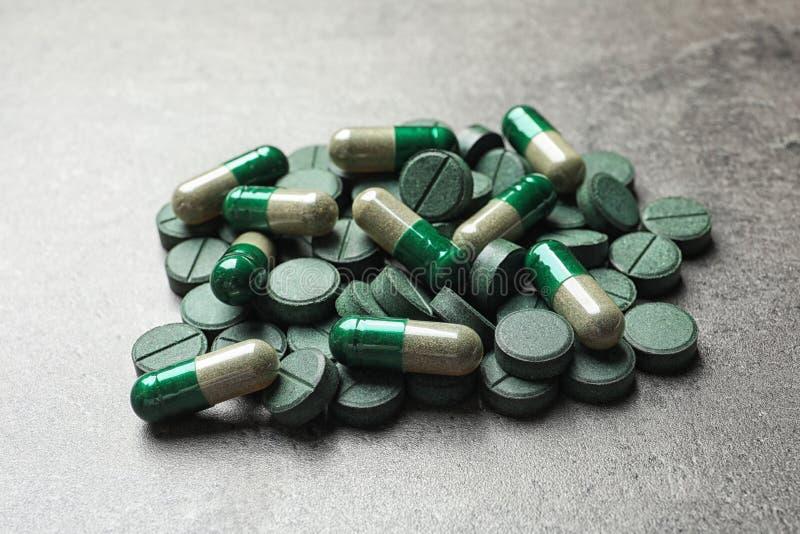 绿色spirulina药片和胶囊 库存图片