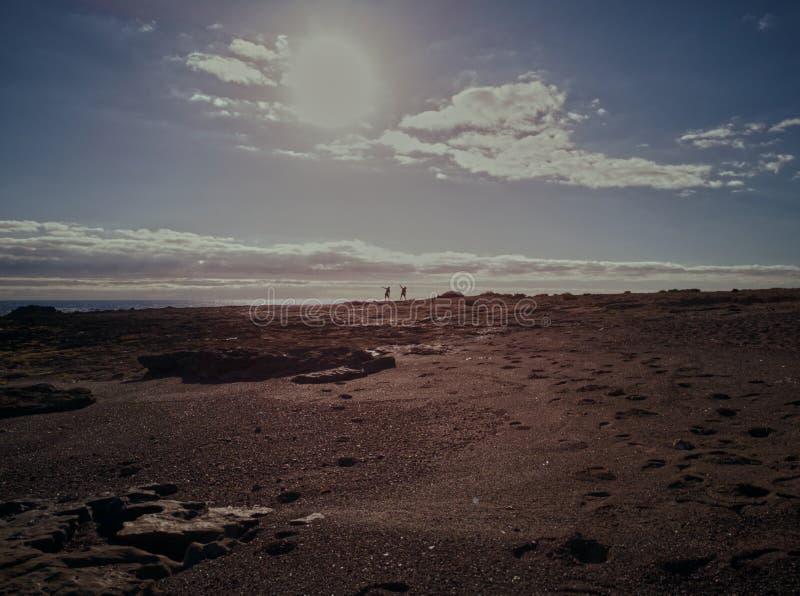 结合在海滩的实践的瑜伽在日落 免版税库存图片