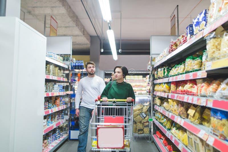 结合走通过有推车的超级市场并且为购物选择产品 在超级市场的家庭购物 库存图片
