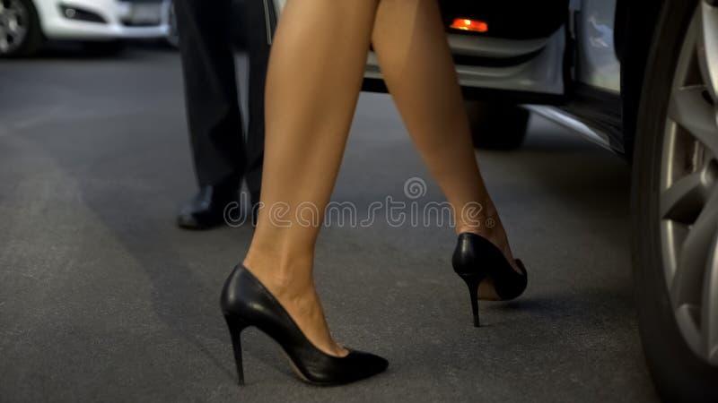 绅士开头车门,进入汽车,关闭的帮助的妇女腿 免版税库存照片
