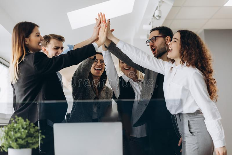 给上流fives姿态的愉快的成功的多种族企业队,他们笑并且欢呼他们的成功 库存图片