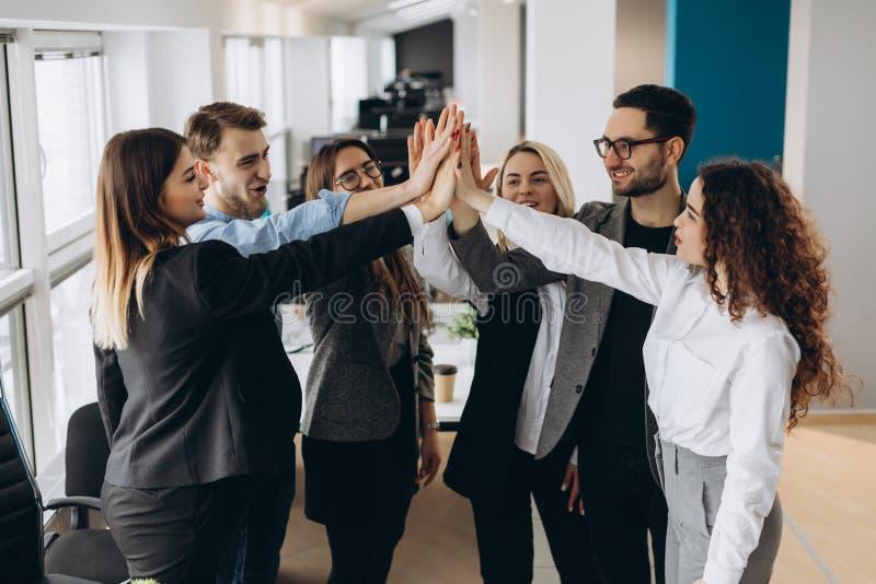 给上流fives姿态的愉快的成功的多种族企业队,他们笑并且欢呼他们的成功 免版税库存图片