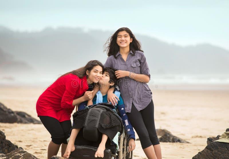 给在海滩的轮椅的残疾兄弟姐姐亲吻 图库摄影