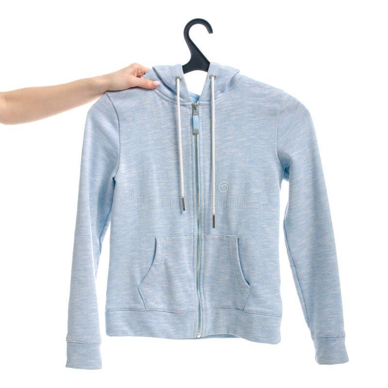 给在锁的蓝色运动衫穿衣在挂衣架女性手上 图库摄影