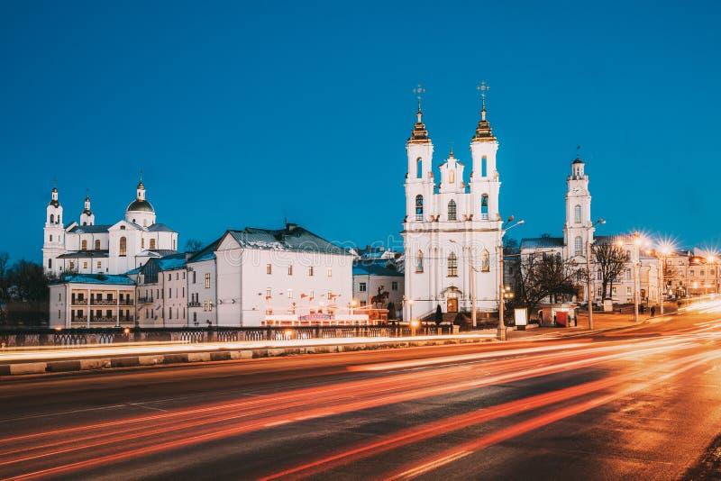 维帖布斯克,白俄罗斯 在街道的交通和圣洁易三仓礼拜堂、圣洁复活教会和政府大厦在晚上或 图库摄影