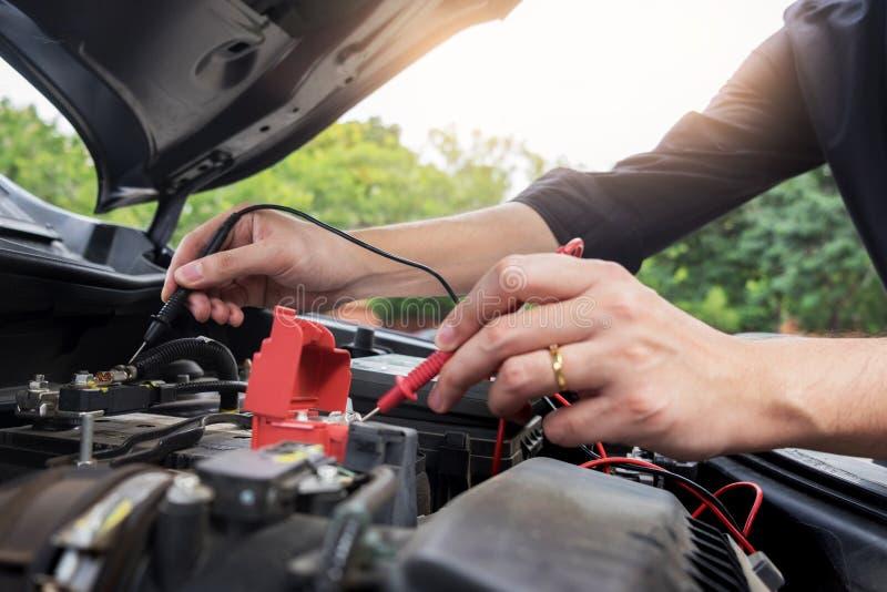 维护汽车修理汽车概念,检查汽车修理师的人工作在车库的汽车敞篷下 免版税库存照片