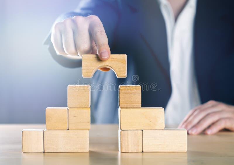 缩小两个塔或党之间的商人差距做由木块;冲突管理或斡旋人概念 免版税库存图片