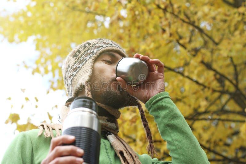 羊毛被编织的帽子的有胡子的人高兴地喝热的茶或咖啡从杯子,底下侧视图,黄色秋天背景  库存照片