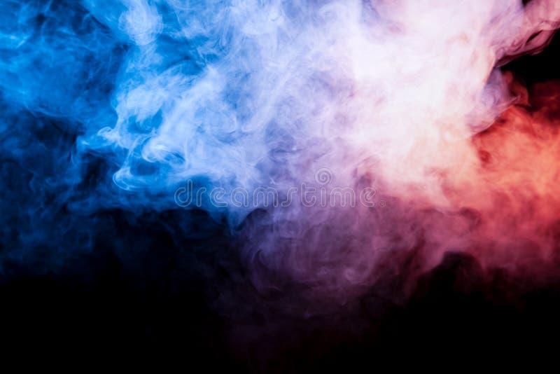 美丽水平的烟柱在蓝色桃红色霓虹明亮的光的和橙色在黑背景呼气在外面 库存图片