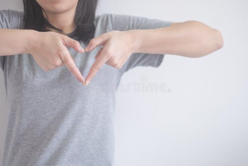 美丽的亚裔妇女显示与手指的姿态心脏在与拷贝空间的白色背景 免版税库存图片