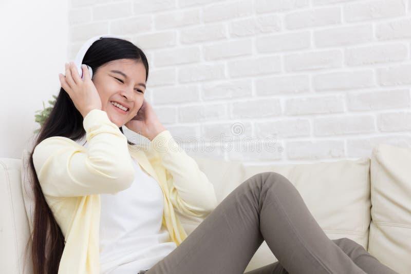 美丽的亚裔年轻女人享用在客厅在家听与耳机的音乐在沙发 库存图片