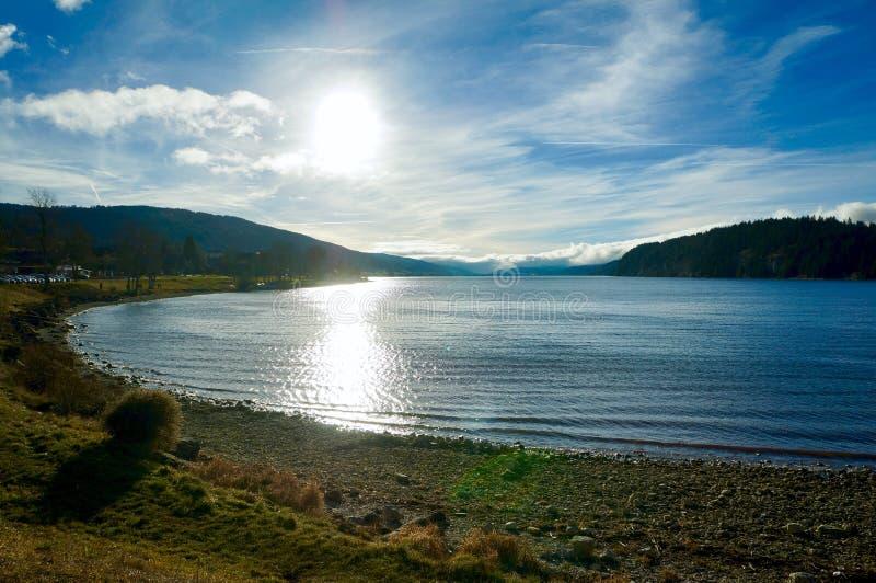 美丽的天空,有光反射的小湖 库存照片