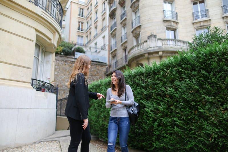 美丽的女孩谈话与保留tabl的外国中国学生 免版税库存图片