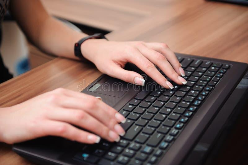 美丽的女商人的手特写镜头与计算机一起使用在她的办公室 免版税库存照片