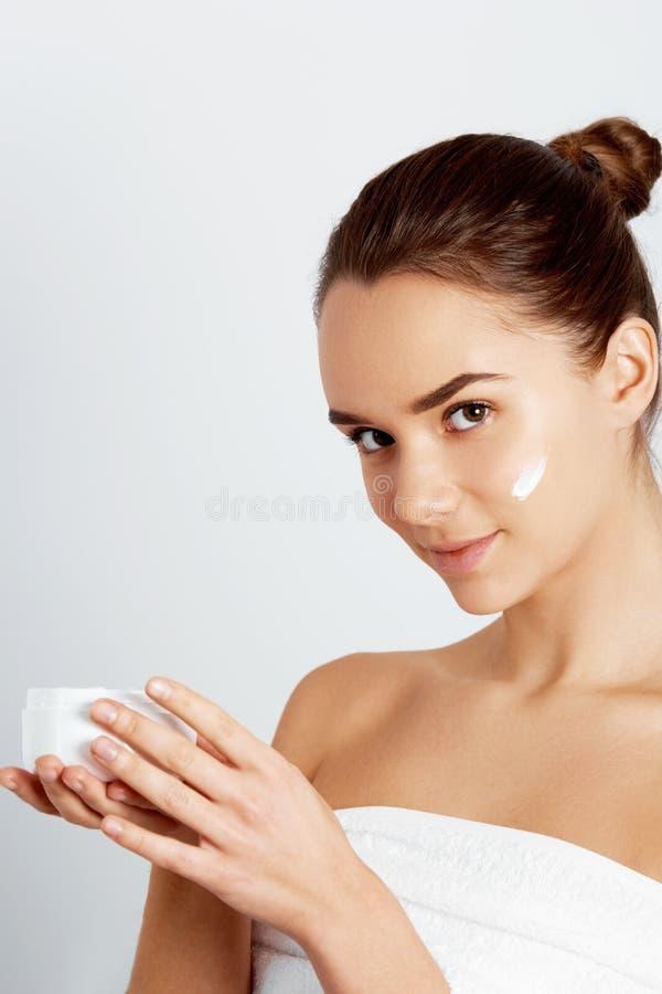 美丽的妇女,演播室的关闭白色背景的 与完善的秀丽女性面孔组成 拿着身体和面孔的奶油 免版税库存图片