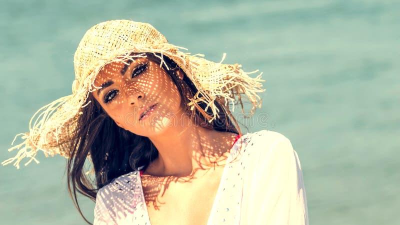 美丽的少妇佩带的夏天帽子画象在海滩的 特写镜头有草帽的画象女孩 免版税库存图片