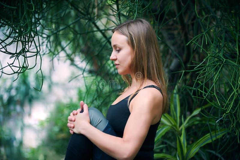 美丽的年轻女人实践瑜伽asana在密林 晴朗的日 库存照片