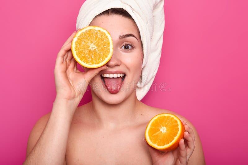 美丽的年轻女人在她的手上举行一半桔子,并且盖子注视与果子的另一个部分 有毛巾的可爱的夫人 库存图片