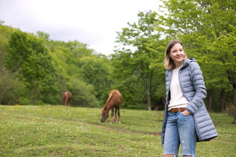 美丽的年轻女人在有马的公园 春天天气 库存图片
