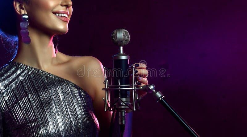 美丽的唱歌的女孩的接近的面孔卷曲非洲的头发歌手唱歌与话筒卡拉OK演唱歌曲 免版税库存图片