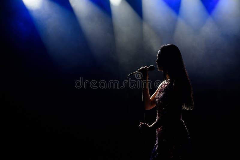 美丽的唱歌的妇女画象黑暗的背景的 免版税库存照片