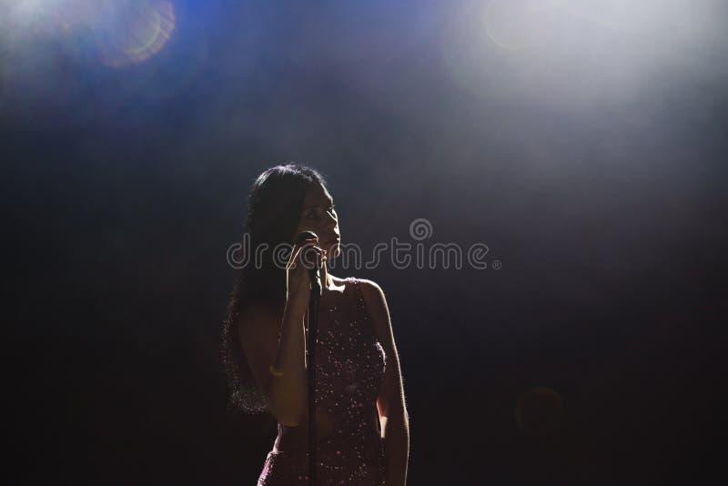 美丽的唱歌的妇女画象黑暗的背景的 免版税图库摄影