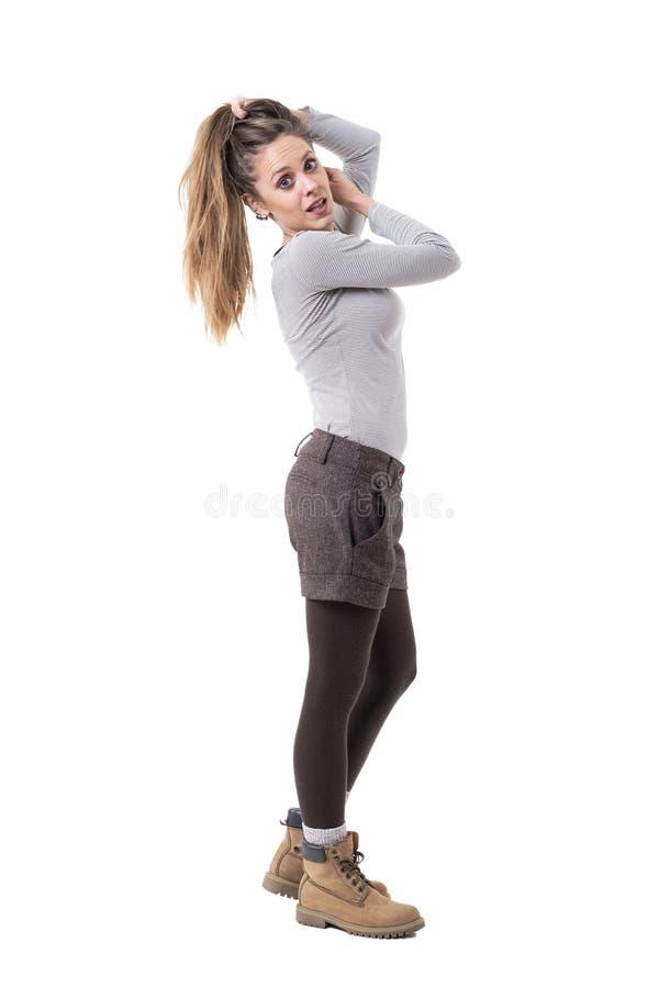 美丽的握在马尾的头发和摆在为照相机的年轻女人时髦的cutie 库存图片