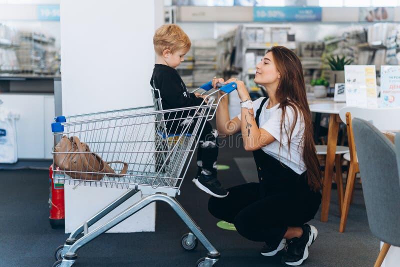 美丽的母亲运载她的超级市场台车的小儿子 库存照片