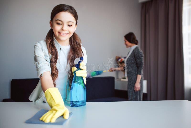 美丽的深色的白种人一起清洗在屋子里的母亲和女儿 女孩举行浪花在手和干净的桌里 免版税库存图片