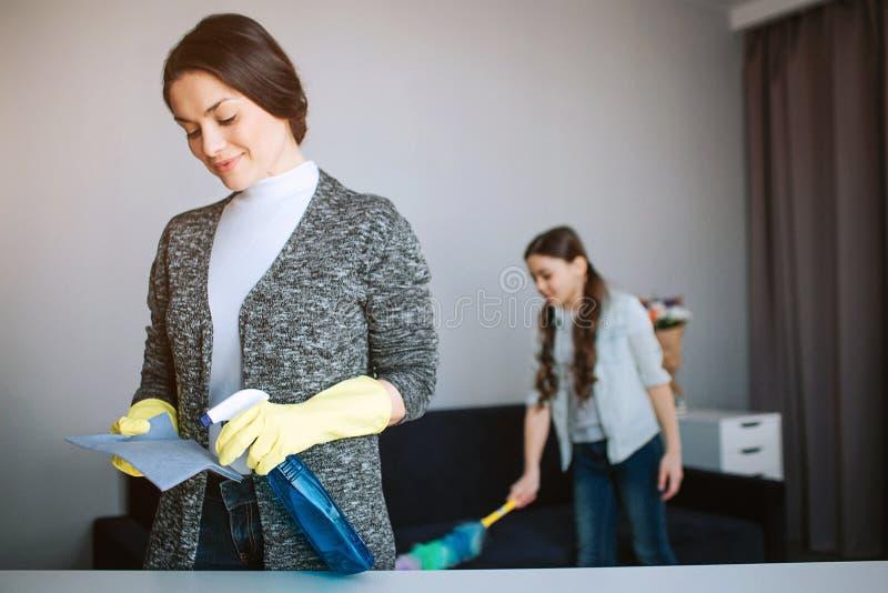 美丽的深色的白种人一起清洗在屋子里的母亲和女儿 在海绵的年轻女人浪花 女孩立场 免版税库存图片