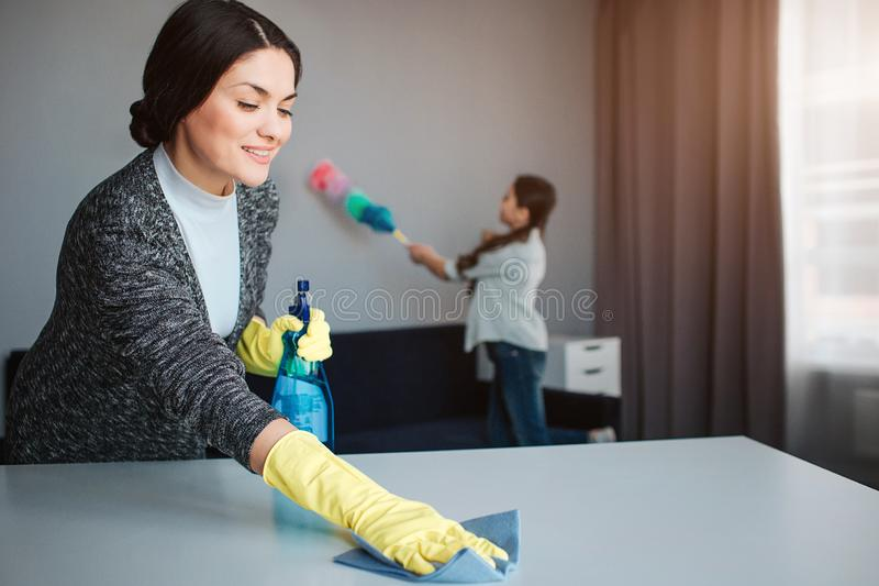 美丽的深色的白种人一起清洗在屋子里的母亲和女儿 雍妇女洗涤物桌和微笑 女孩 库存照片