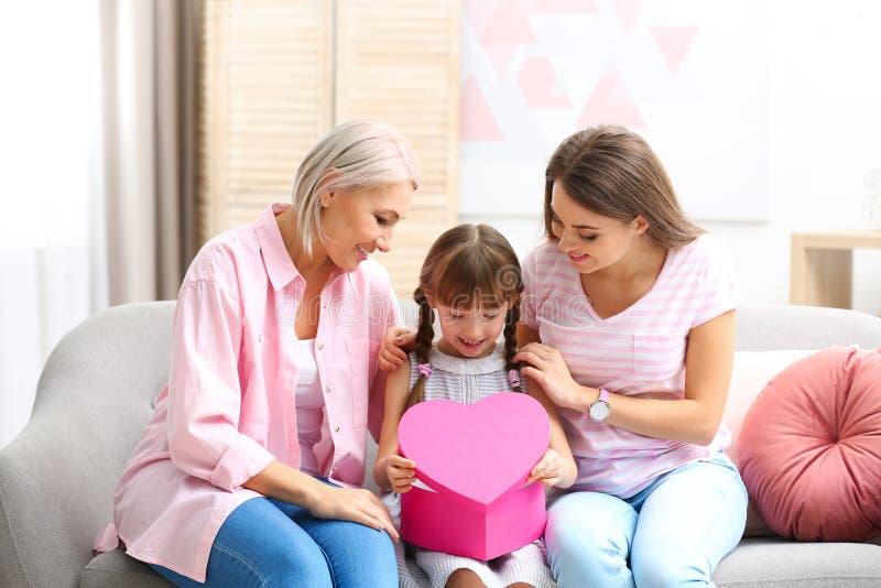 美丽的成熟夫人、女儿和孙有礼物盒的在家 库存照片