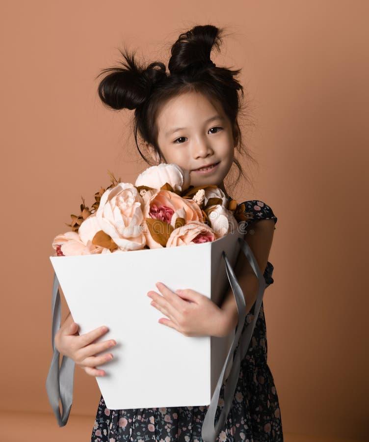 美丽的春天礼服的逗人喜爱的矮小的亚裔女孩拥抱她得到大白花中介子的一个大篮子  图库摄影