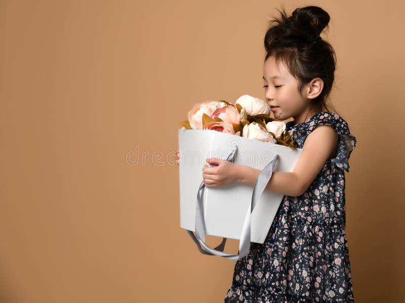 美丽的春天礼服的逗人喜爱的矮小的亚裔女孩拿着大白花中介子一个大篮子并且小心地精美地嗅到它 库存图片