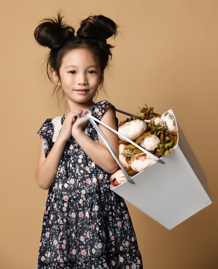 美丽的春天礼服的逗人喜爱的矮小的亚裔女孩站立与大白花中介子一个大篮子在她的肩膀的 库存照片