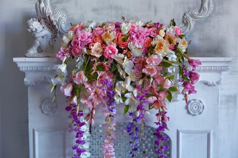 美丽的明亮的混杂的花花束在白色壁炉的 可爱的花 专业卖花人的工作 库存图片