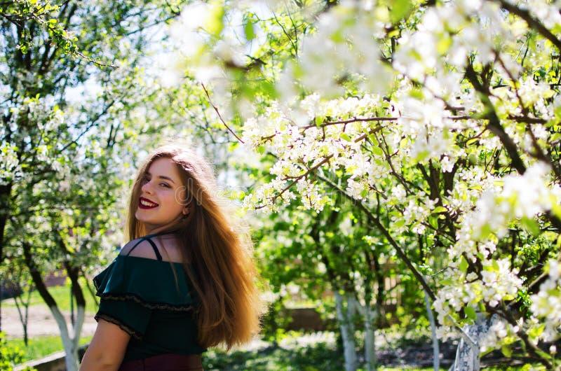 美丽的愉快的女孩在春天在新鲜空气的 免版税库存图片